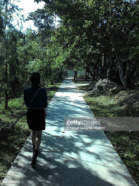 Rear View Of Young Woman Walking On Path In Botanical Garden