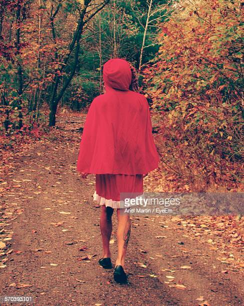 Rear View Of Young Woman Wearing Red Riding Hood Costume Walking On Pathway