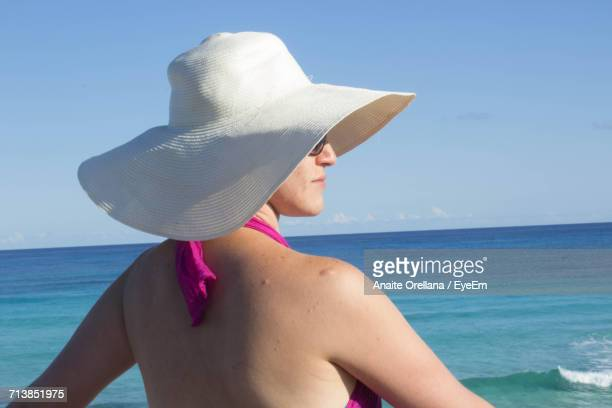 Rear View Of Young Woman Wearing Sun Hat Standing By Sea Against Sky