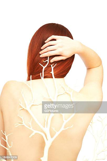 Rear view of young woman with branch on her back