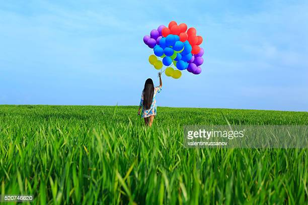 Rear view of young woman with colored balloons