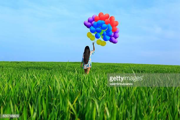 Rückansicht des Junge Frau mit farbigen Ballons