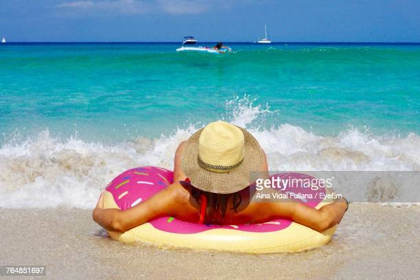 Rear View Of Young Woman With Inflatable Ring Relaxing At Beach During Sunny Day
