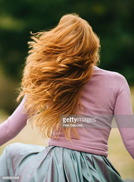 Rear view of young woman with long red hair twirling in park