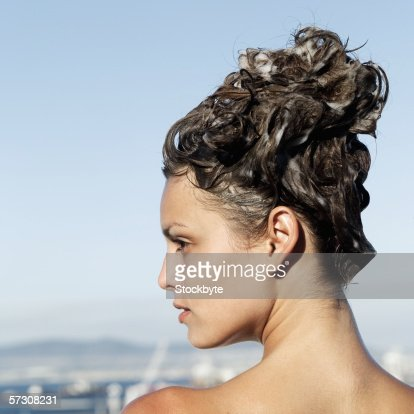 Rear view of young woman with shampoo in hair : Stock Photo