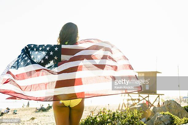 Rear view of young woman wrapped in American flag on Newport Beach, California, USA