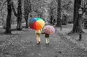 Rear view on mother and son with multi colored umbrellas in isolated color walking hand in hand in black and white park. Maybe useful as a symbol for guidance and security in childhood.