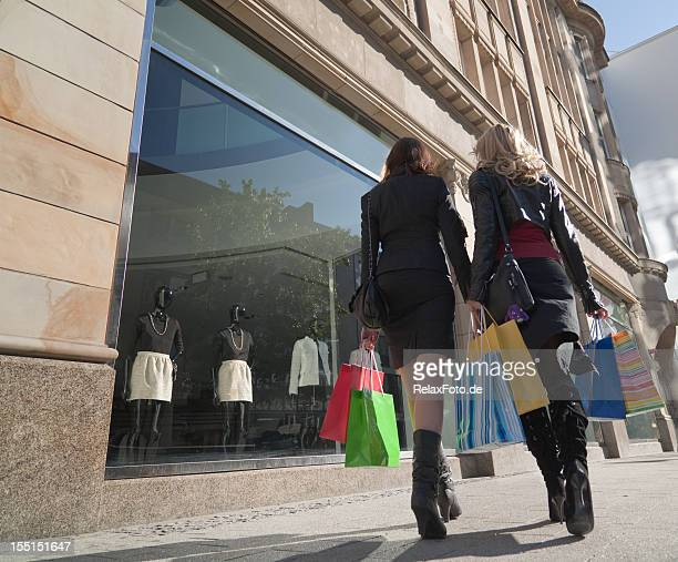 Rear view on two women with shopping bags