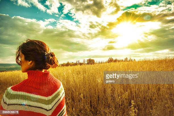 rear view on woman with poncho standing in summer field