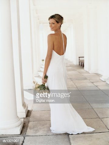 Rear View Portrait of a Bride Standing in a Colonnade and Holding a Bouquet of White Roses