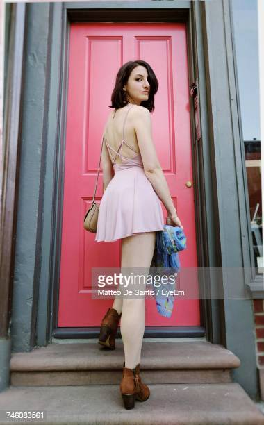 Rear View Portrait Of Beautiful Woman Standing Against Red Door