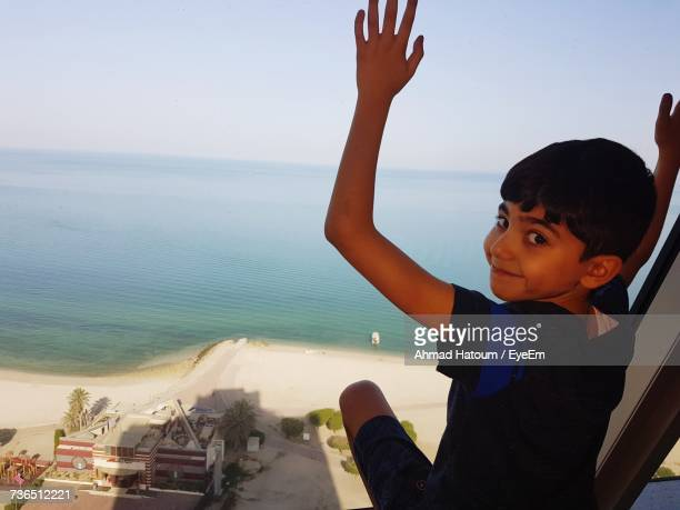 Rear View Portrait Of Boy Sitting By Glass Window At Home With Sea In Background