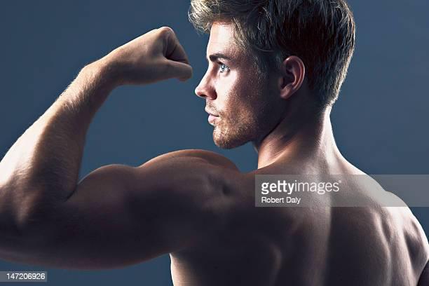 Rückansicht Porträt eines Mannes flexing Bizeps Muskeln