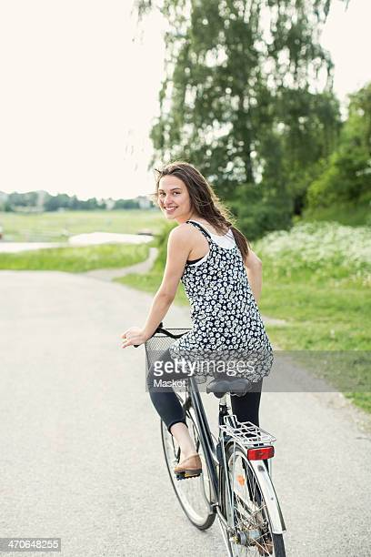 Rear view portrait of young woman cycling on country road