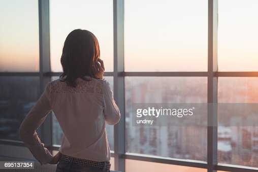 Rear view portrait of young worker speaking using cell phone, looking out the window. Female having business call, busy at her workplace in evening. : Stock Photo