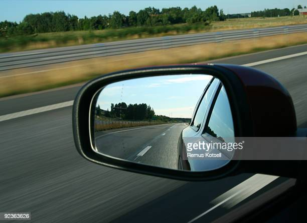Rear view reflected in a car mirror