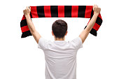 Rear view shot of a teenage soccer fan holding a scarf isolated on white background
