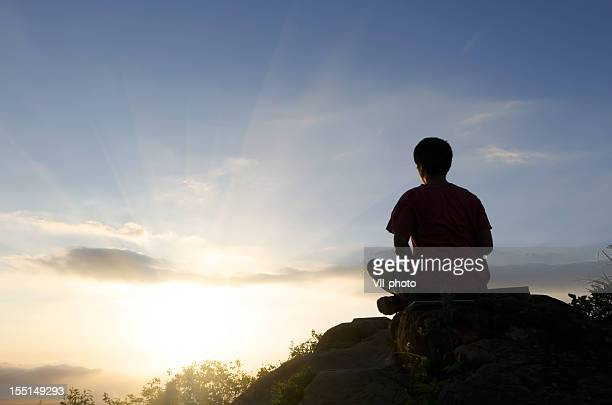 Rear view silhouette of man sitting atop peak at sunset