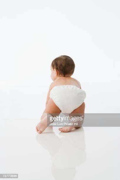Rear view studio shot of baby crawling
