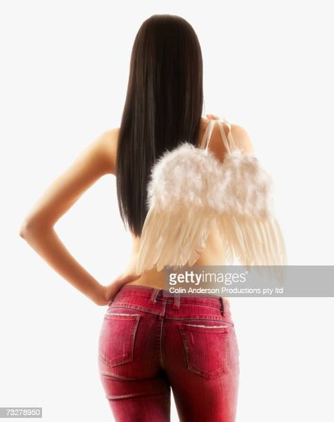 Rear view studio shot of woman holding wings over shoulder