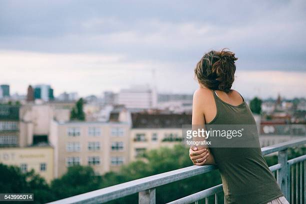 rear view: young woman leans against railing, looks to Skyline
