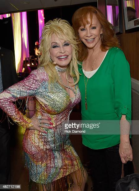 Reba McEntire visits Dolly Parton backstage during Dolly Parton Pure Simple Benefiting The Opry Trust Fund at Ryman Auditorium on August 1 2015 in...