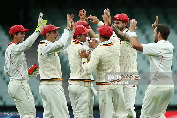 Rebacks players celebrate with Chadd Sayers after he got the wicket of Ryan Carters of the NSW Blues during day one of the Sheffield Shield match...