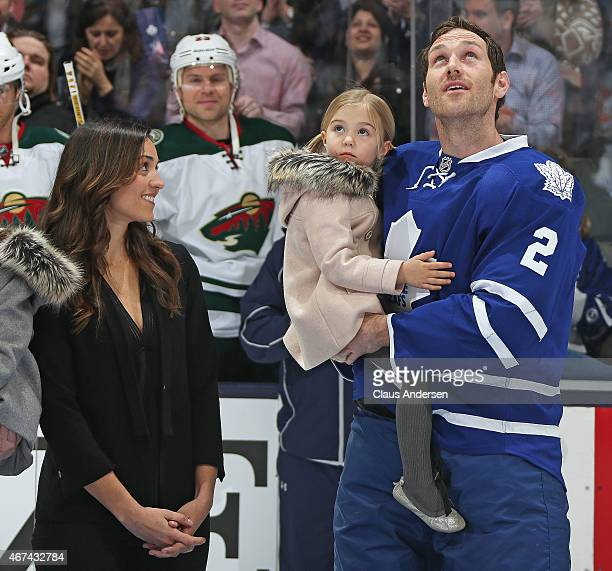 Rebecca Brewer proudly watches her husband Eric Brewer of the Toronto Maple Leafs receive recognition for playing 1000 NHL games prior to play...