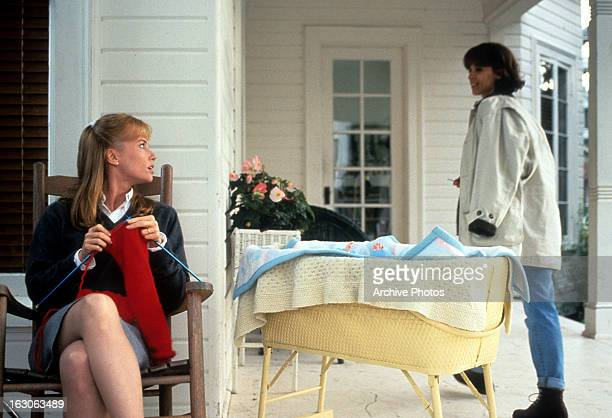 Rebecca De Mornay knits as she glances back at Annabella Sciorra in a scene from the film 'The Hand That Rocks the Cradle' 1992