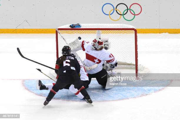 Rebecca Johnston of Canada scores a goal against Florence Schelling and Sandra Thalmann of Switzerland in the second period during the Women's Ice...