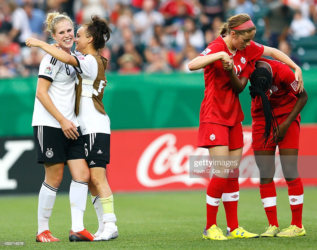Rebecca Knaak and Lina Magull of Germany celebrate their 2-0 win as Janine Beckie of Canada consoles Kadeisha Buchanan after the FIFA U-20 Women's World Cup Canada 2014 Quarter Final match between Germany and Canada at Commonwealth Stadium on August 16, 2014 in Edmonton, Canada.