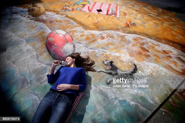 Rebecca Marren from Blackrock Dublin enjoys a icecream on the chalk beach created by 3D street artist Julian Beevor on the pavement in the IFCS...