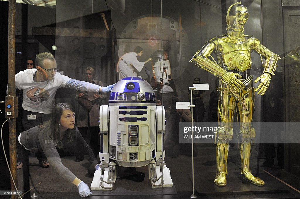 Rebecca Melius (2/L) from the Museum of Science in Boston and Nick Grotty from Museum Victoria (L), place R2-D2 next to C-3PO - both used during the filming of Star Wars - securely in a display at Melbourne's Scienceworks at a new exhibition called 'Star Wars: Where Science Meets Imagination', on May 19, 2009. It is the first exhibition to showcase costumes and props from all six Star Wars movies while exploring cutting-edge research and modern technologies that could one day make the fantasy world of Star Wars a reality. The exhibition explores the fantasy technologies depicted in the Star Wars movies, the real science behind them, and the latest research that may someday lead to remarkable real-world equivalents. Visitors will encounter over 80 artefacts, including props, costumes and models from all six Star Wars films and examples of comparable real-world technologies. Authentic costumes and props from the entire Star Wars aga, such as Princess Leia�s famous white dress, Darth Vader�s menacing black armour, a full-sized R2-D2, a stormtrooper uniform and Luke Skywalker�s landspeeder. AFP PHOTO/William WEST