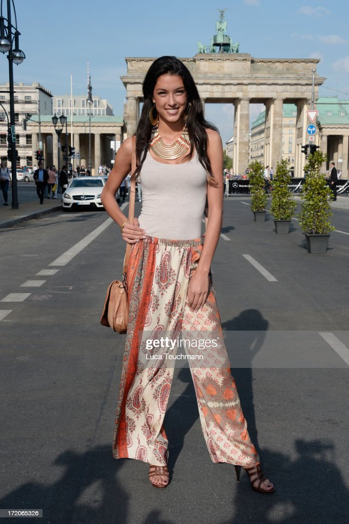Rebecca Mir wears shoes from Valentina and pants from Zara as she attends the Mercedes-Benz Fashion week spring and summer 2014 at the Brandenburg Gate on July 1, 2013 in Berlin, Germany.
