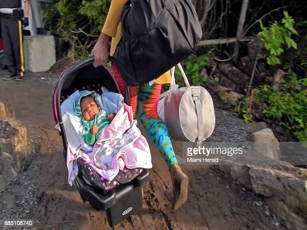 Rebecca Paul carrying an infant walks across a dirt and gravel path on the US and Canadian border along Roxham Road on Sunday Aug 13 2017 Thousands...