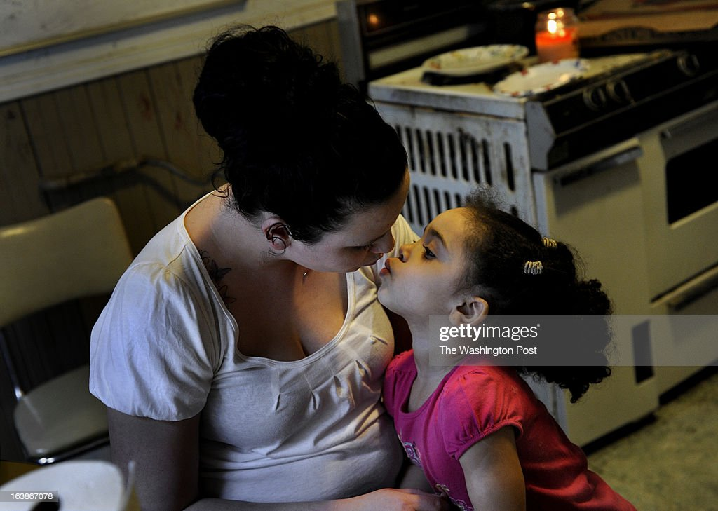 Rebecka Ortiz gives a kiss to her daughter Sariah, 3, in the kitchen after they had put away all of the groceries they'd bought (with food stamps) on a trip to the store. Many families and individuals in Woonsocket, Rhode Island are needy and take part in the SNAP (food stamps) program. Photo by Michael S. Williamson/The Washington Post via Getty Images