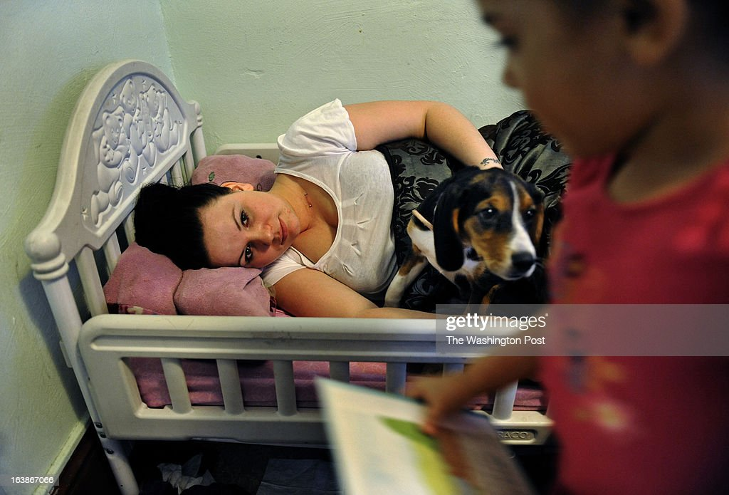 Rebecka Ortiz hoped to take a quick nap (with dog Roxy) while her husband was still at home (he was due for work soon) but her 3 year-old daughter Sariah wanted her to read a book. Many families and individuals in Woonsocket, Rhode Island are needy and take part in the SNAP (food stamps) program. Photo by Michael S. Williamson/The Washington Post via Getty Images