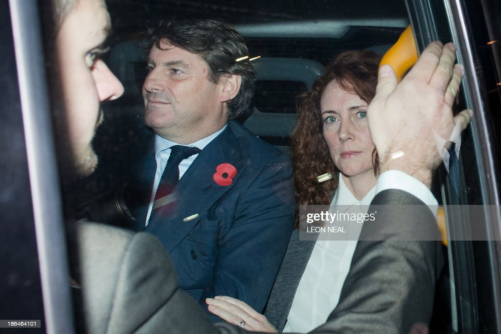 Rebekah Brooks (R), former News International chief executive, and her husband Charlie (L) leave the Old Bailey court in London on October 31, 2013 after another day's hearing in the phone hacking trial. Former News of the World editors Rebekah Brooks and Andy Coulson were having an affair throughout much of the time they were allegedly involved in phone hacking at the Rupert Murdoch-owned tabloid, their trial heard on October 31.