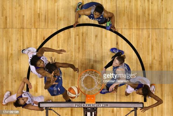 Rebekkah Brunson of the Minnesota Lynx lays up a shot under pressure from Krystal Thomas of the Phoenix Mercury during the first half of the WNBA...
