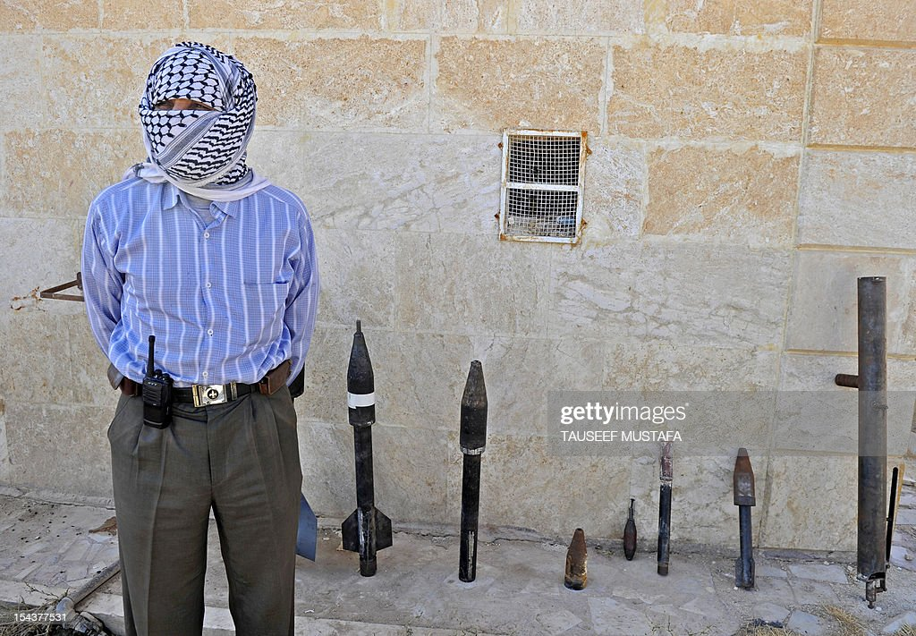 Rebel arms maker Abu al-Fadhel shows off a row of homemade weapons including a hand-grenade, a portable rocket-launcher, and various rockets with explosive warheads at a location in Aleppo province on October 17, 2012. Lightly-armed Syrian rebels who face the warplanes, artillery and tanks of President Bashar al-Assad's forces have turned to making their own weapons to fill major gaps in their armouries.