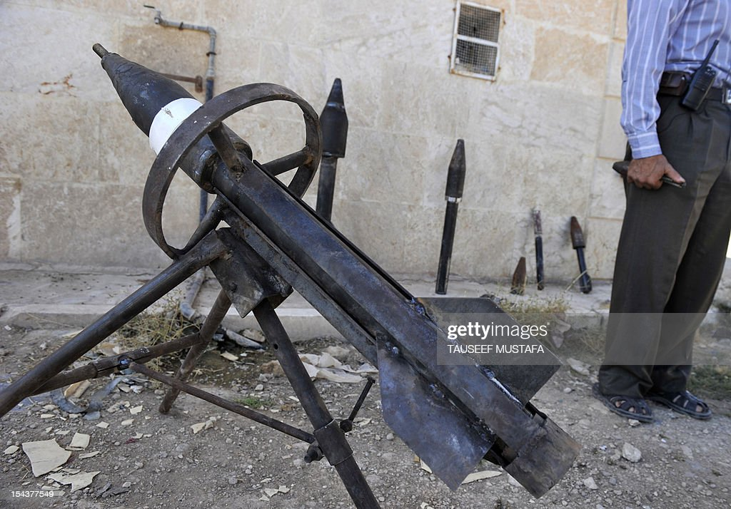 Rebel arms maker Abu al-Fadhel shows off a row of homemade weapons including a hand-grenade, a portable rocket-launcher, and various rockets with explosive warheads at a location in Aleppo province on October 17, 2012. Lightly-armed Syrian rebels who face the warplanes, artillery and tanks of President Bashar al-Assad's forces have turned to making their own weapons to fill major gaps in their armouries. AFP PHOTO/TAUSEEF MUSTAFA