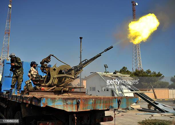 A rebel celebrates by shooting an antiaircraft gun in Ras Jdir west Libya on August 27 2011 Libyan rebels captured the Ras Jdir border post on the...