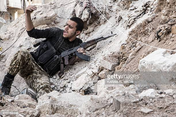 A rebel fighter calls on his comrades during clashes with regime forces in the northern Syrian city of Aleppo on October 31 2014 Syria accused Turkey...