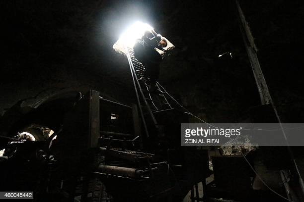 A rebel fighter climbs down a ladder after monitoring government soldiers positions in the old city of Aleppo on December 6 2014 Aleppo Syria's...
