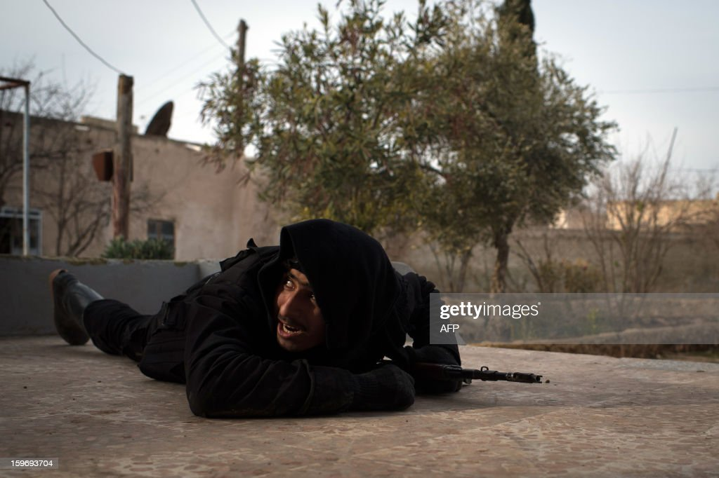 A Rebel fighter ducks for cover from government jet fighters in the city of Aleppo on January 18, 2013. UN leader Ban Ki-moon warned that Syria is in a 'death spiral', as his top humanitarian and human rights officials pleaded with the UN Security Council to take firmer action. AFP PHOTO / EDOUARD ELIAS