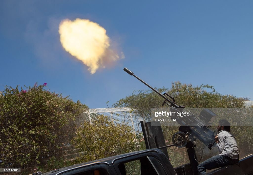 A rebel fighter fires a 23mm anti-aircraft gun from the back of a pick-up truck as a Syrian Airforce plane flies overhead during clashes between the rebels and pro-government troops on the outskirts of the northern city of Aleppo, on July 4, 2013. Syria's President Bashar al-Assad accused the West of sending 'takfiri terrorist groups' to his country as a way to get rid of them, in an interview with a Syrian daily published.