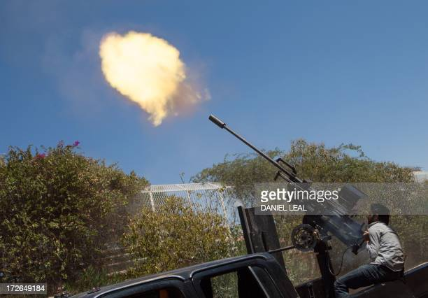 A rebel fighter fires a 23mm antiaircraft gun from the back of a pickup truck as a Syrian Airforce plane flies overhead during clashes between the...