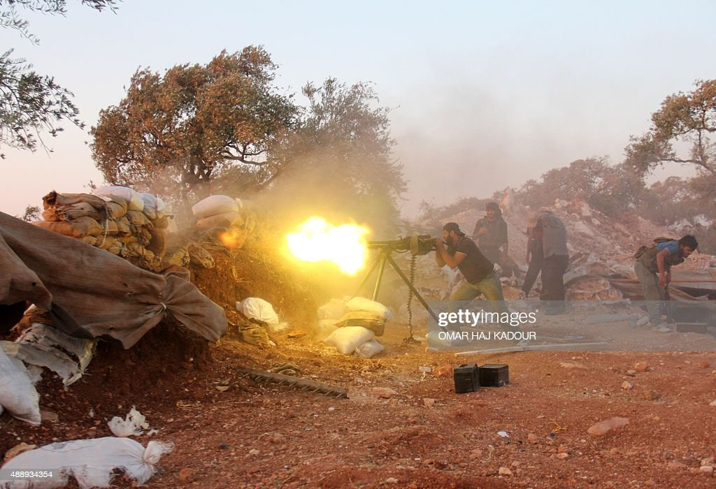 A rebel fighter fires a heavy machine gun during clashes with government forces and proregime shabiha militiamen in the outskirts of Syria's...