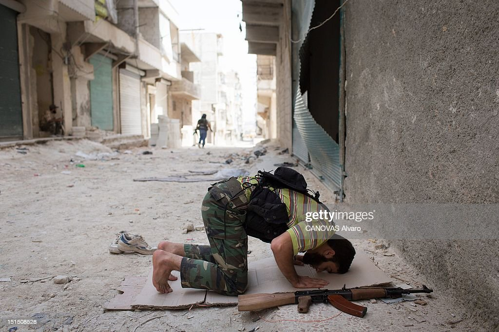 A rebel fighter kneels to pray in the street before returning to fight in the Amreya district on August 30, 2012 in Aleppo, Syria. Government forces loyal to President Bashar al-Assad, continue to bombard Syria's largest city with strikes from the air and artillery, seeking to weaken the resolve of rebel Free Syrian Army forces in the region.