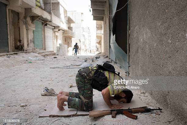 A rebel fighter kneels to pray in the street before returning to fight in the Amreya district on August 30 2012 in Aleppo Syria Government forces...